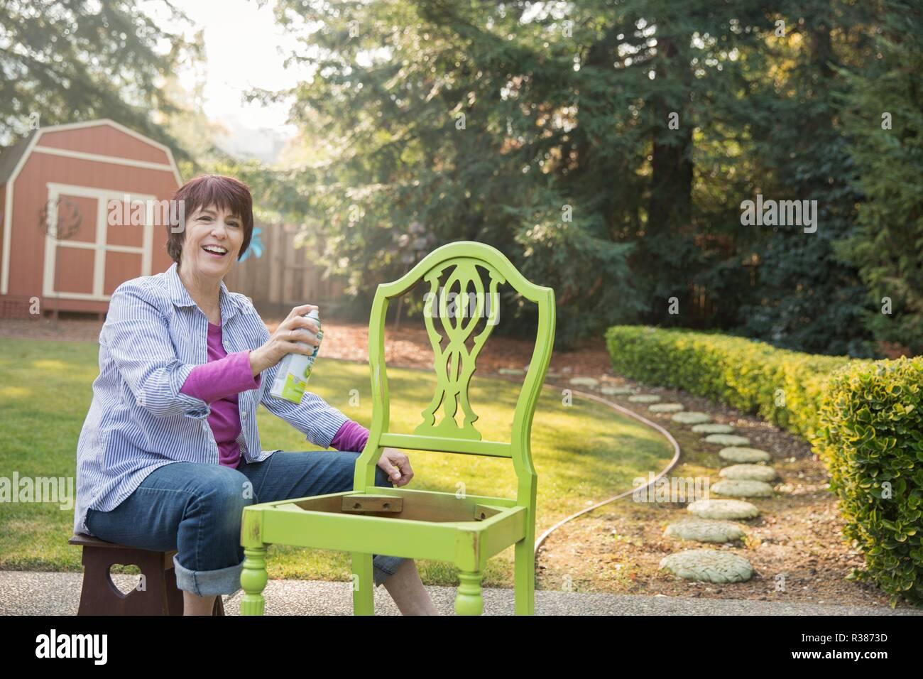 A mature women artist restoring a chair. - Stock Image