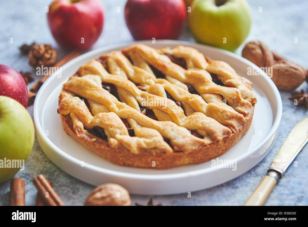 Tasty sweet homemade apple pie cake with cinnamon sticks, walnuts and apples - Stock Image