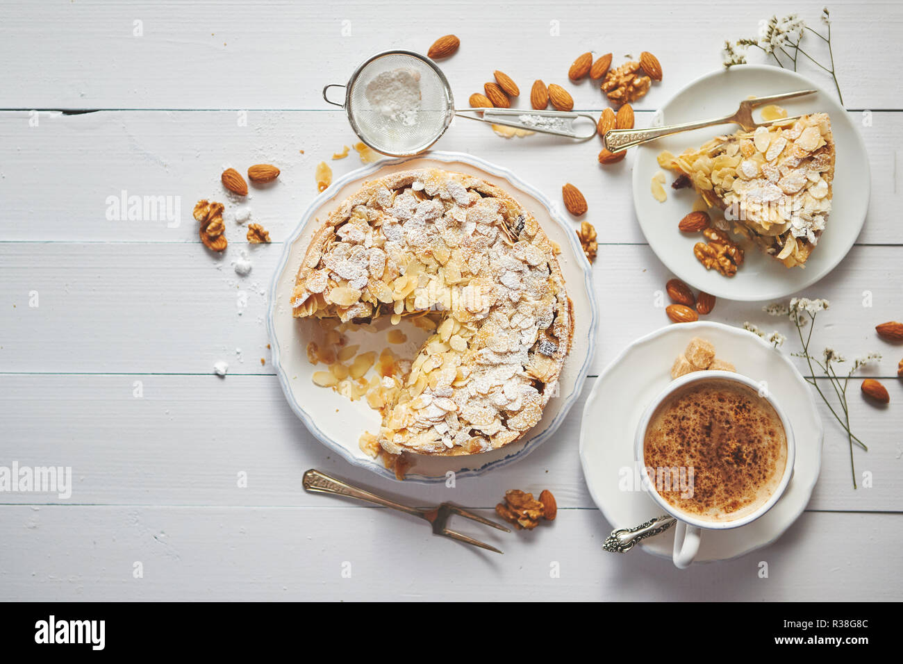 Whole delicious apple cake with almonds served on wooden table - Stock Image
