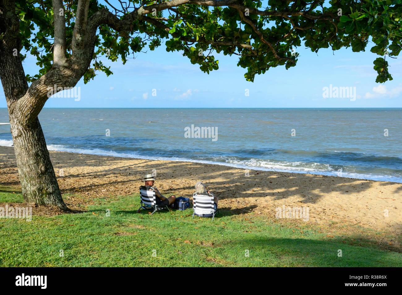 Senior couple relaxing on the beach, Trinity Beach, Cairns Northern Beaches, Far North Queensland, FNQ, QLD, Australia - Stock Image