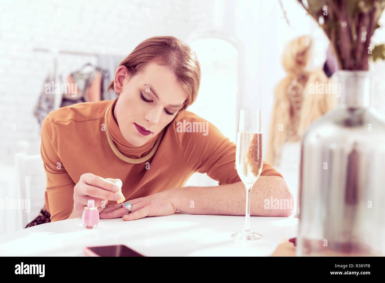 Beautiful short-haired transgender man painting his nail - Stock Image