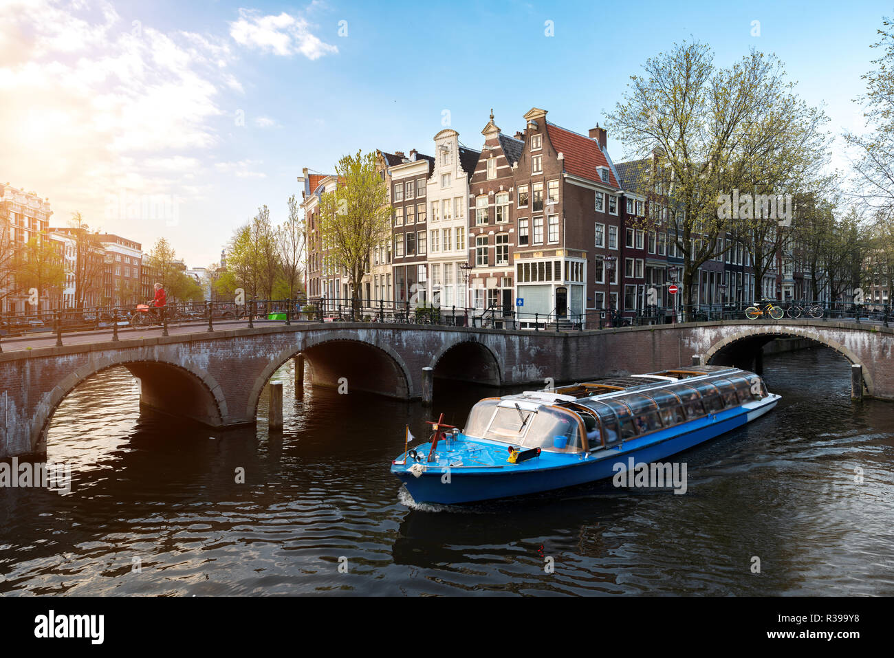Amsterdam canal cruise ship with Netherlands traditional house in Amsterdam, Netherlands. - Stock Image