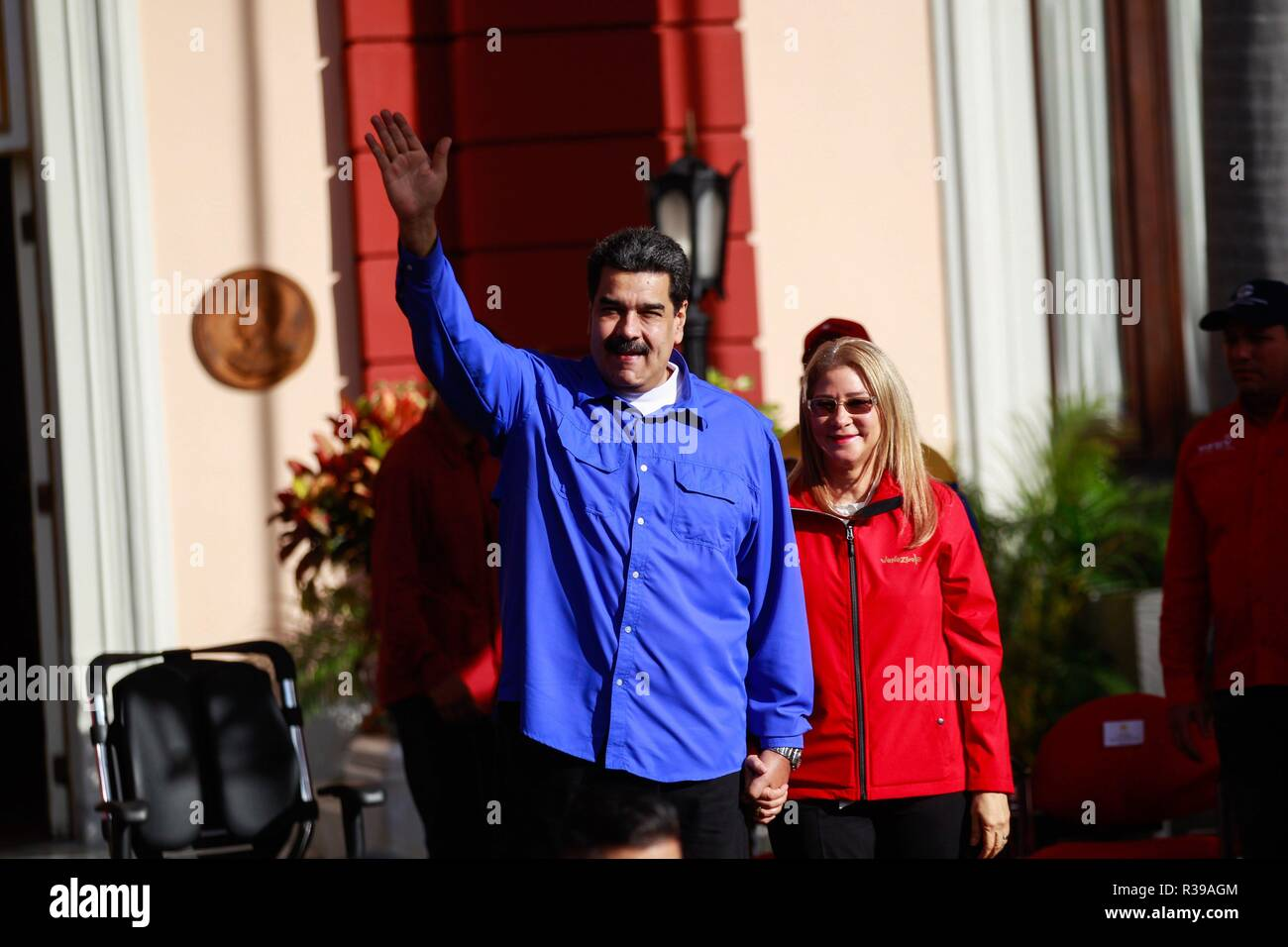 Caracas, Venezuela. 21st Nov, 2018. Venezuelan president, Nicolas Maduro (L), greets his supporters accompanied by his wife, Cilia Flores (R), during an act for the celebration of Student Day, in Caracas, Venezuela, 21 November 2018. Maduro asked university students to join the militias and prepare for the defense of the country 'with weapons in hand' if necessary, in the face of possible attacks by 'imperialism' and 'oligarchy', as he usually refers to the United States and the opposition. Credit: CRISTIAN HERNANDEZ/EFE/Alamy Live News - Stock Image