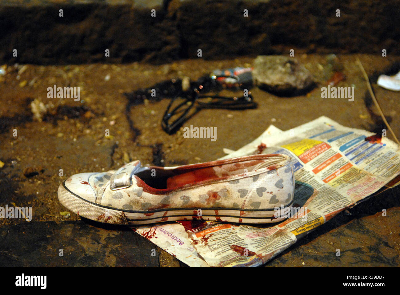 One shoe with blood stains at CST train station after Mumbai was attacked by Deccan Mujahideen terrorists in South Mumbai India 26/11/2008. Terrorists killed 100 people and wounded more than 200 in a series of coordinated attacks across India?s financial hub Mumbai as Heavily armed gunmen in groups of two to four opened fire with automatic weapons and lobbed grenades in 10 places in south Mumbai, including the five-star Taj and Trident hotels, the city?s main railway terminus, a hospital, a cafe, a pub and a cinema hall. Photo: Dinodia    (c) dpa - Report      usage worldwide - Stock Image