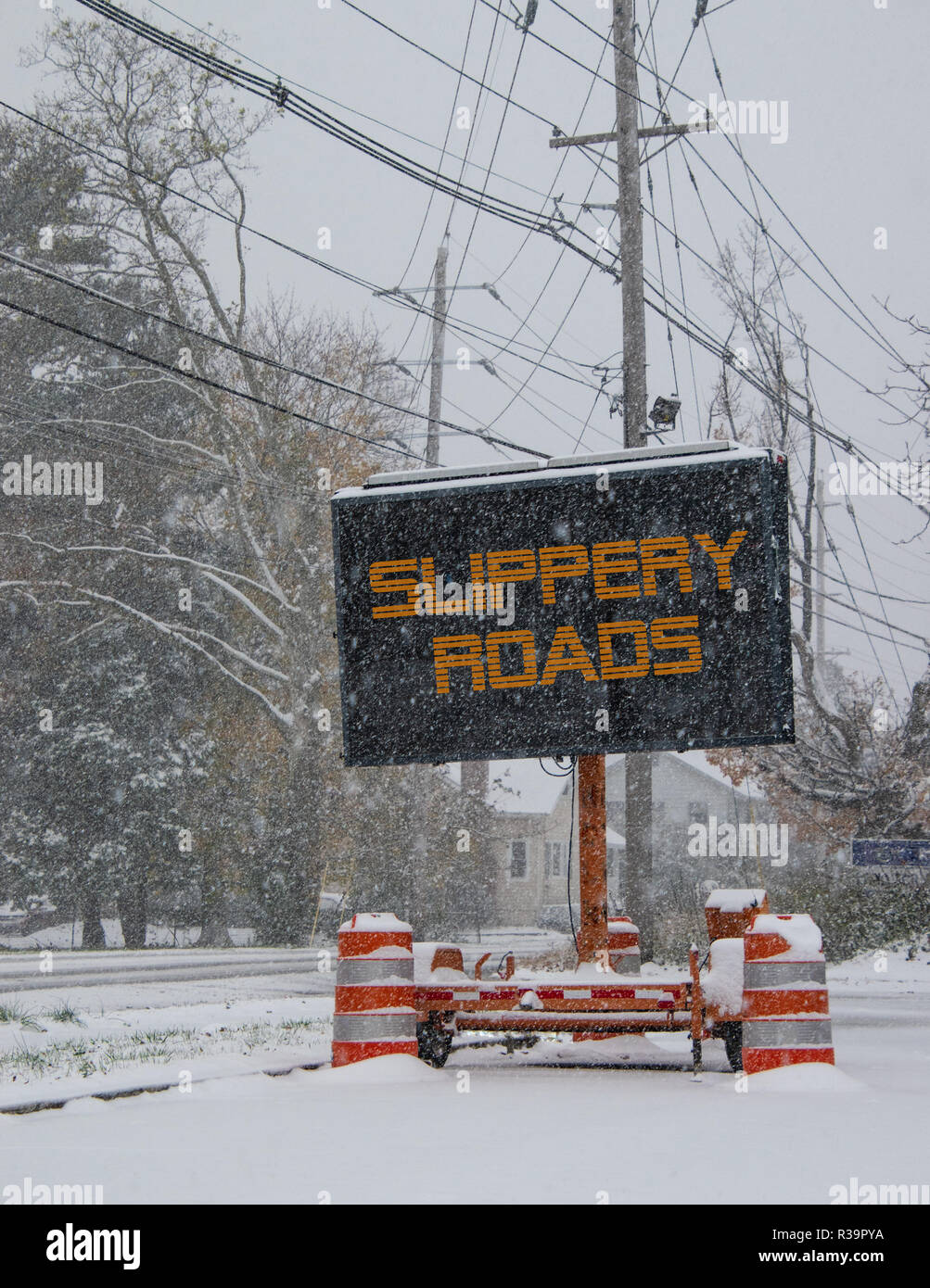 Electric road traffic mobile sign by the side of a snow covered road in winter with snow falling warning of slippery roads - Stock Image
