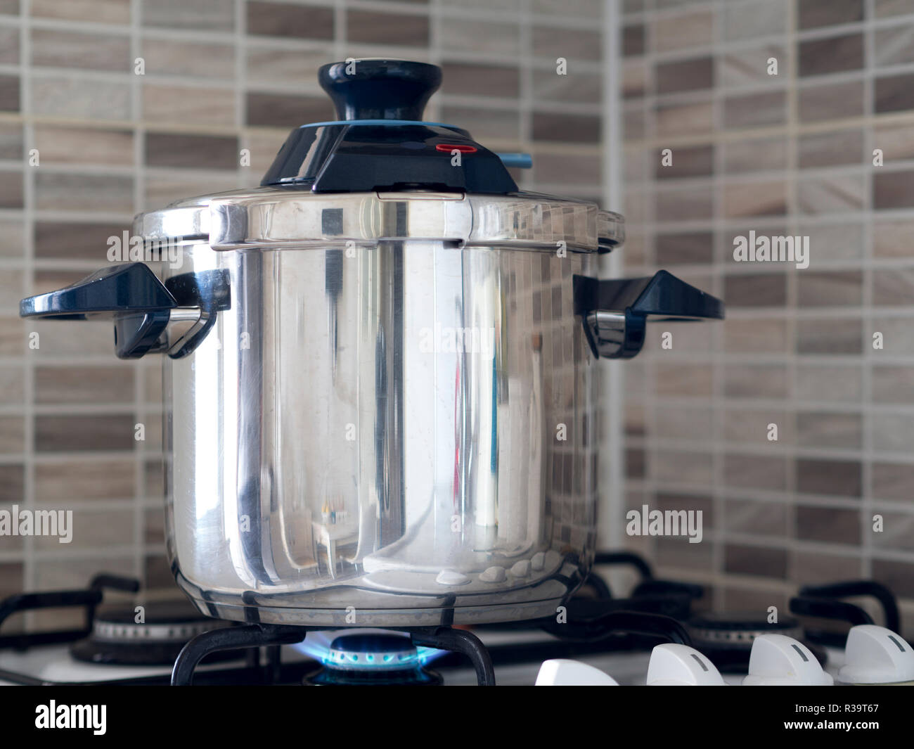 Metallic steel pressure cooker standing on the oven in the kitchen and cooking being cooked - Stock Image