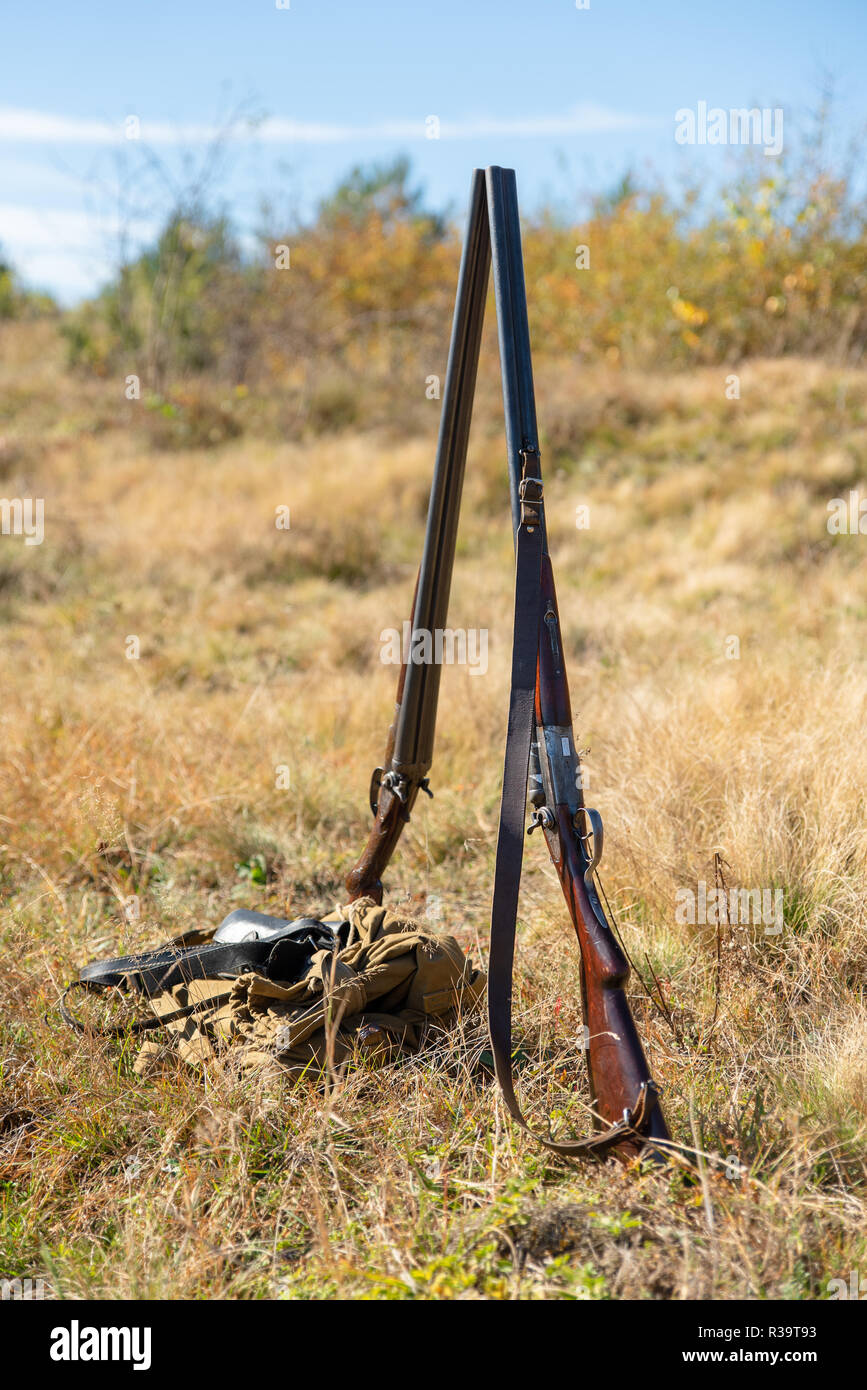 Two hunting double-barreled shotgun stand side by side in the middle of nature, retro rifle. Natural landscape. Concept of hunting, outdoor sports, hobbies and lifestyle Stock Photo