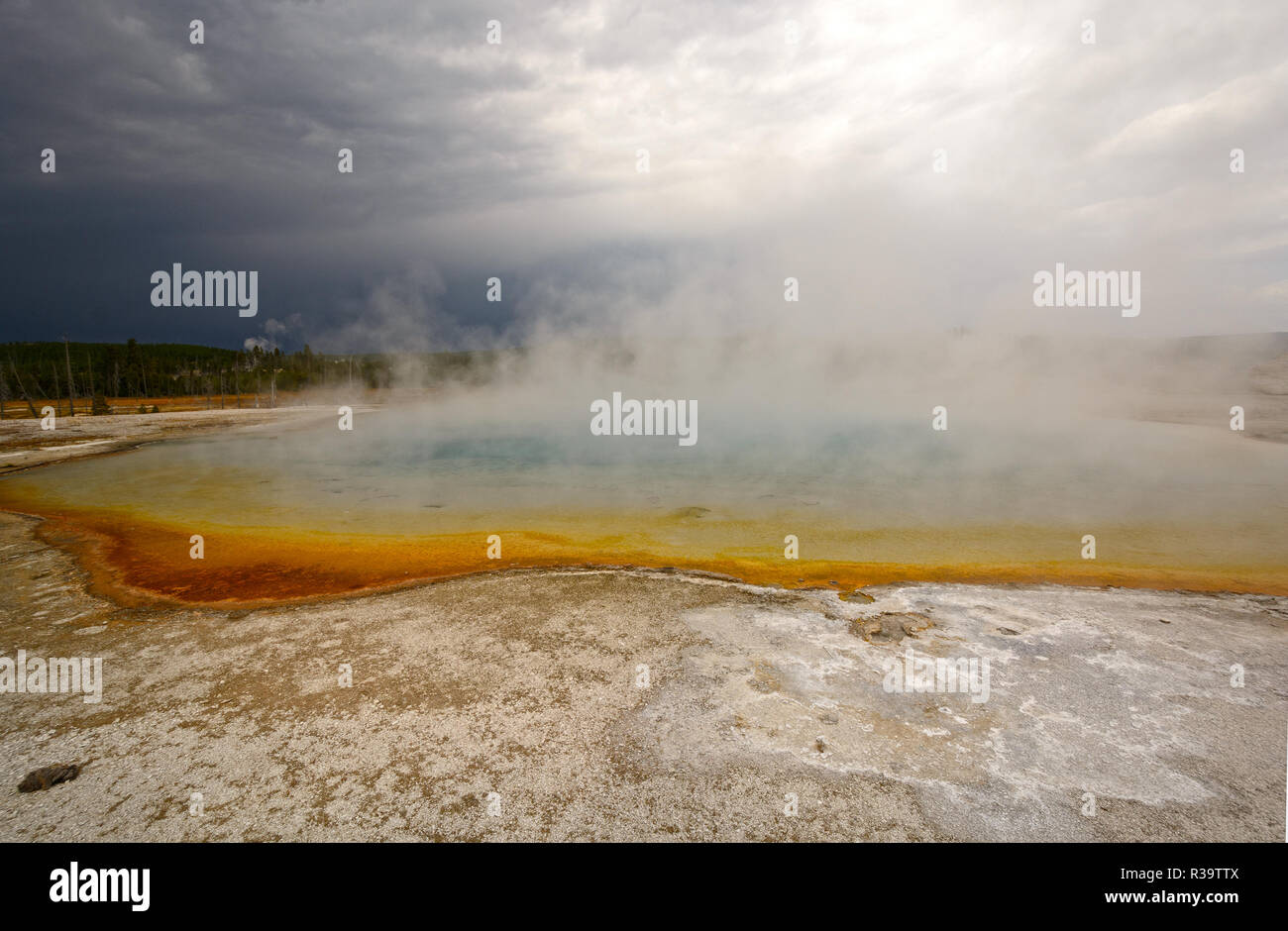 Storm Clouds over Sapphire Pool in Biscuit Basin in Yellowstone National park in Wyoming - Stock Image