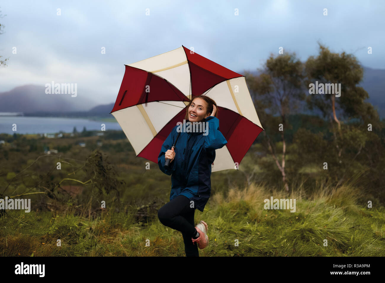 Smiling girl standing outdoor on the green grass, cold wet autumn weather. Woman holding big red and white umbrella. Mountains on the background, lake Stock Photo