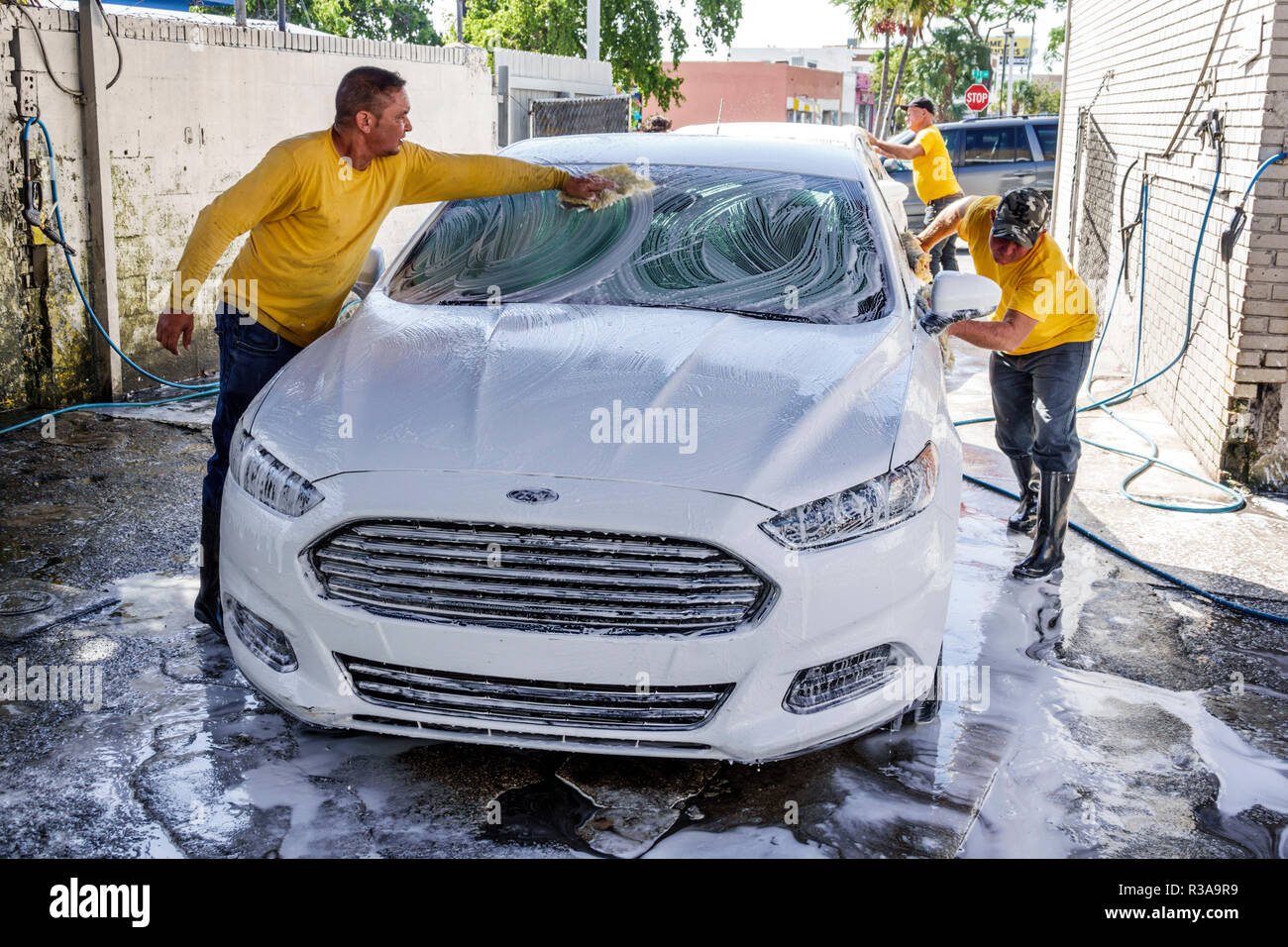 Miami Florida Little Havana car wash white Ford Fusion Hispanic man working cleaning soap soaping wiping teamwork - Stock Image