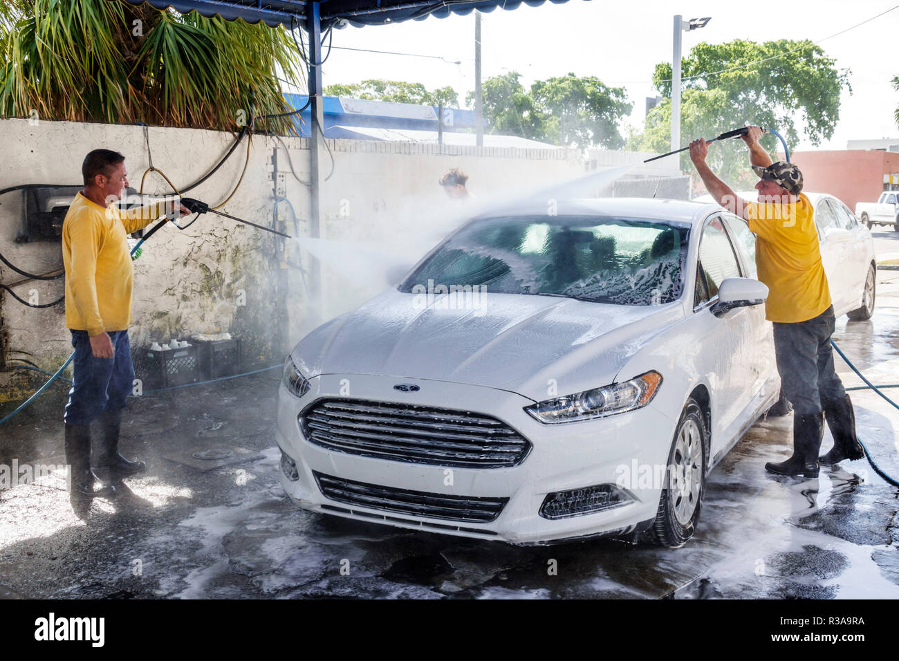 Miami Florida Little Havana car wash white Ford Fusion Hispanic man working cleaning water hose high pressure spray spraying teamwork - Stock Image