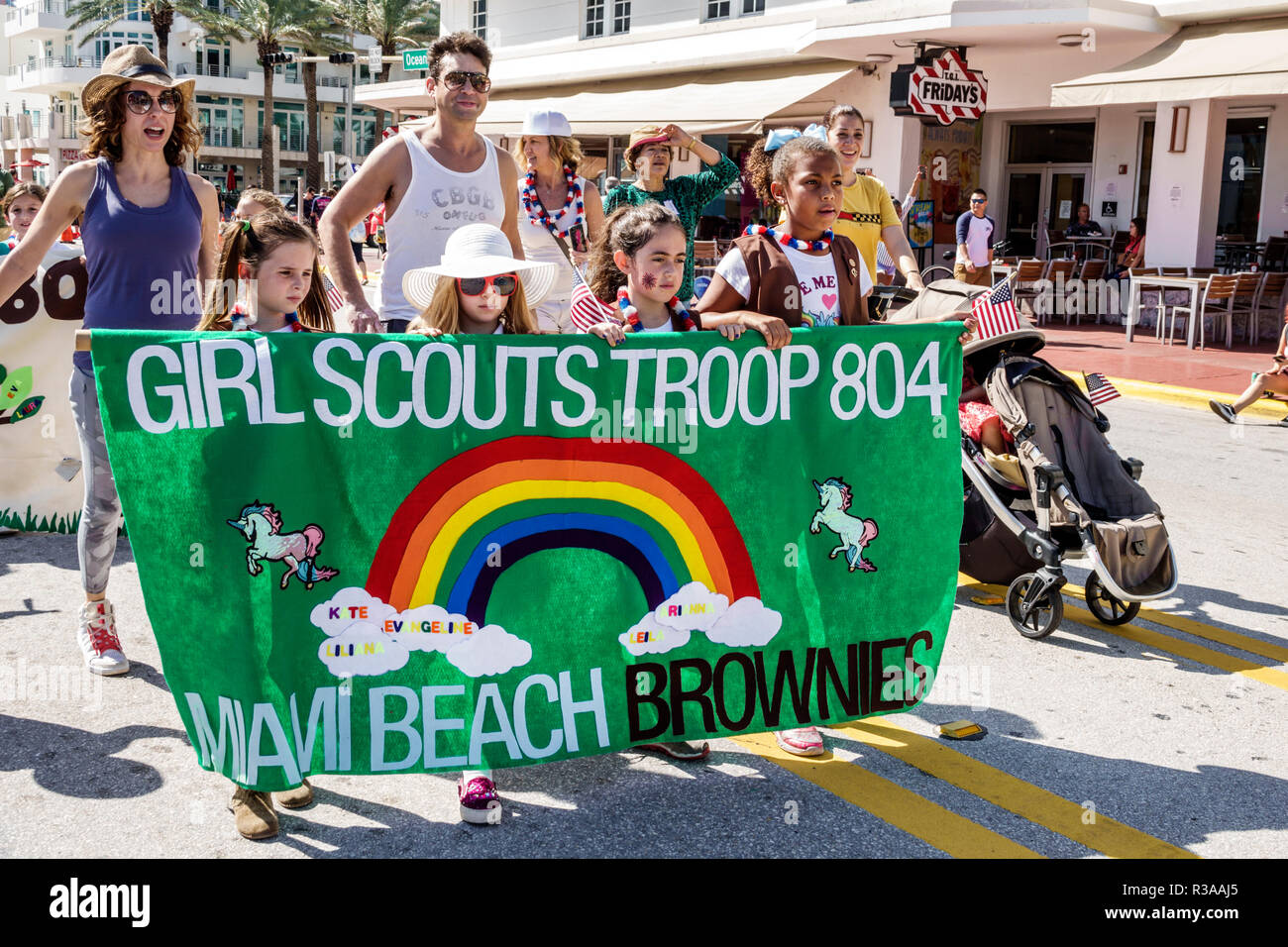 Miami Beach Florida Ocean Drive Veterans Day Parade activities Brownies Girl Scouts troop marching banner Black - Stock Image