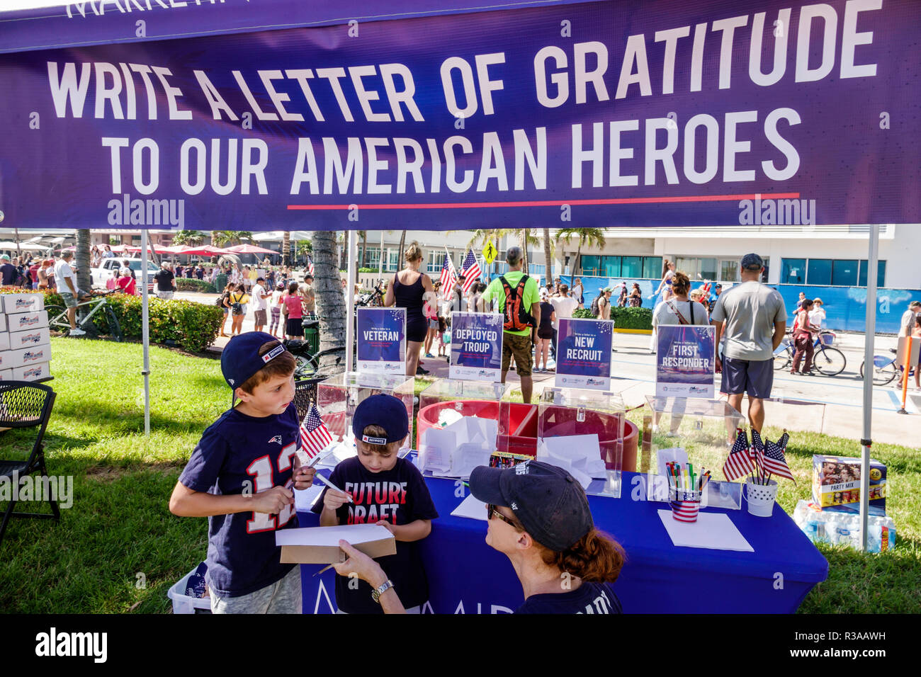 Miami Beach Florida Ocean Drive Veterans Day Parade activities write letter gratitude American heroes first responders mother boy son writing - Stock Image