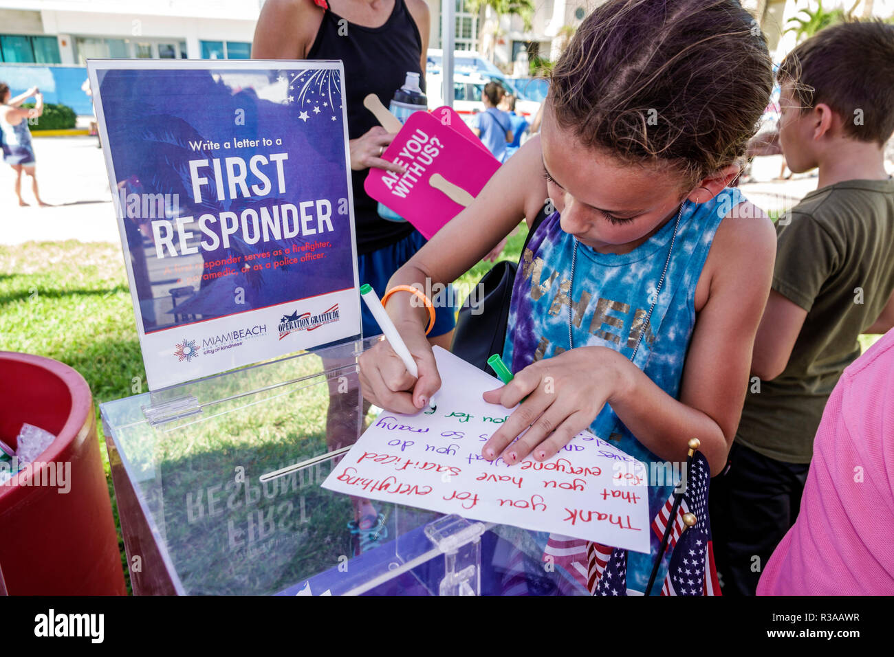 Miami Beach Florida Ocean Drive Veterans Day Parade activities write letter gratitude American heroes first responders girl writing - Stock Image