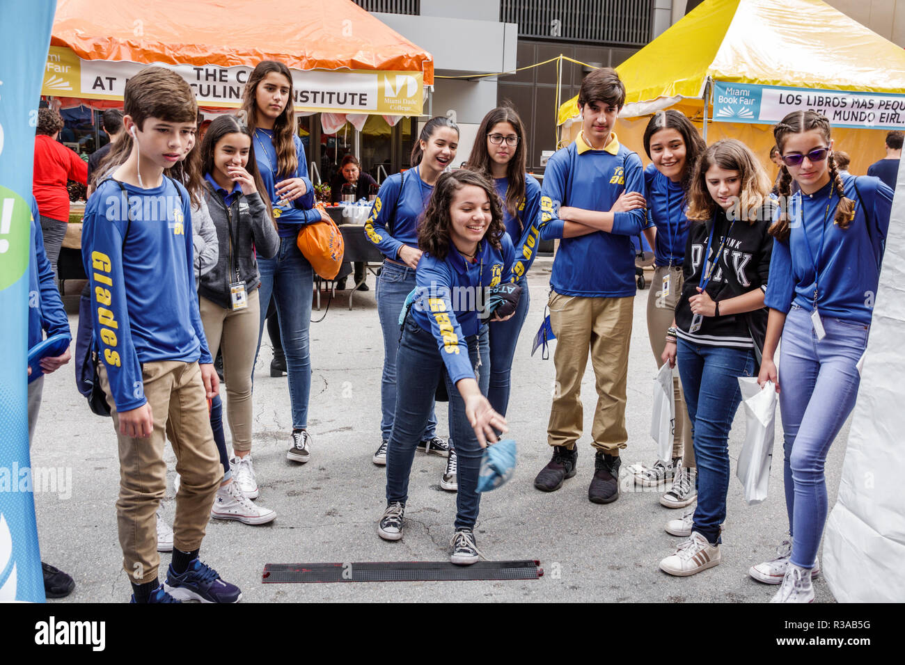 Miami Miami Florida-Dade College Book Fair annual event booths stalls vendors booksellers books sale shopping bean bag toss teen boy girl student watc - Stock Image