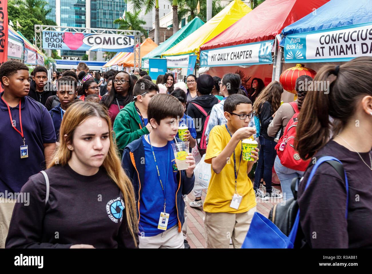 Miami Miami Florida-Dade College Book Fair annual event booths stalls vendors booksellers books sale shopping student boy girl Hispanic Black friends - Stock Image