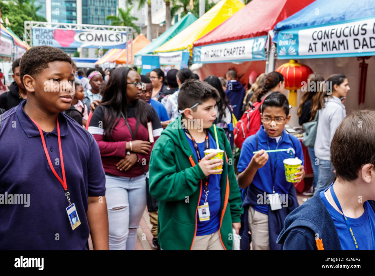 Miami Miami Florida-Dade College Book Fair annual event booths stalls vendors booksellers books sale shopping student boy Hispanic Black friends - Stock Image