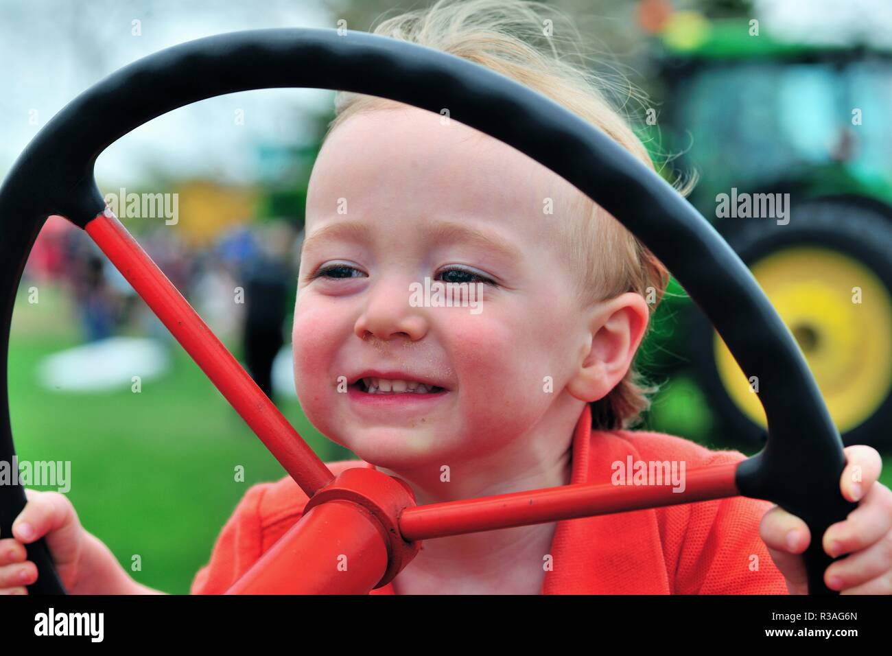 St. Charles, Illinois, USA. Little boy enjoying steering a stationary tractor at a touch-a-tractor event hosted by a farm bureau. - Stock Image