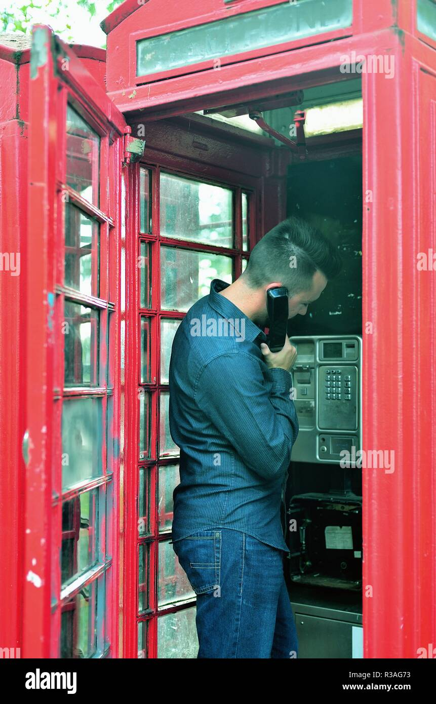 London, England, United Kingdom. Man using a traditional red telephone box along Park Lane on the edge of Hyde Park in London's West End. - Stock Image
