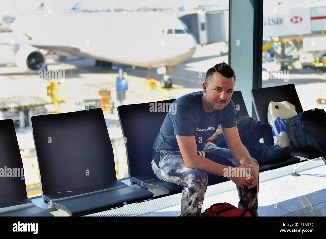 London, England, United Kingdom. International departing passenger waiting at his gate prior to boarding a flight. - Stock Image
