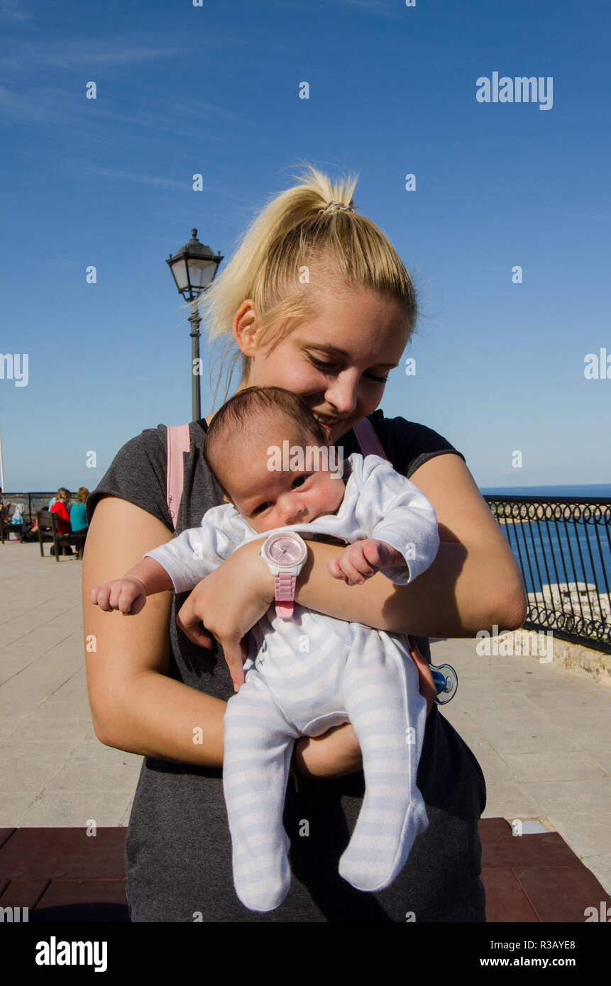 Young blond mom holding one month old baby boy blue sky sunny day mellieha