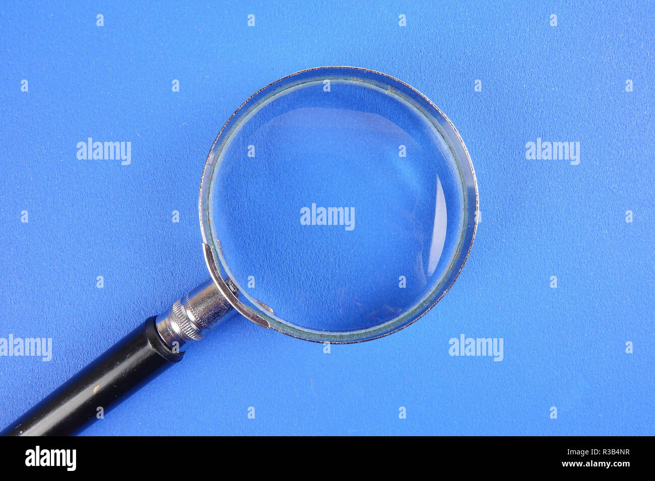 Hand holding magnify glass over a blue background - Stock Image