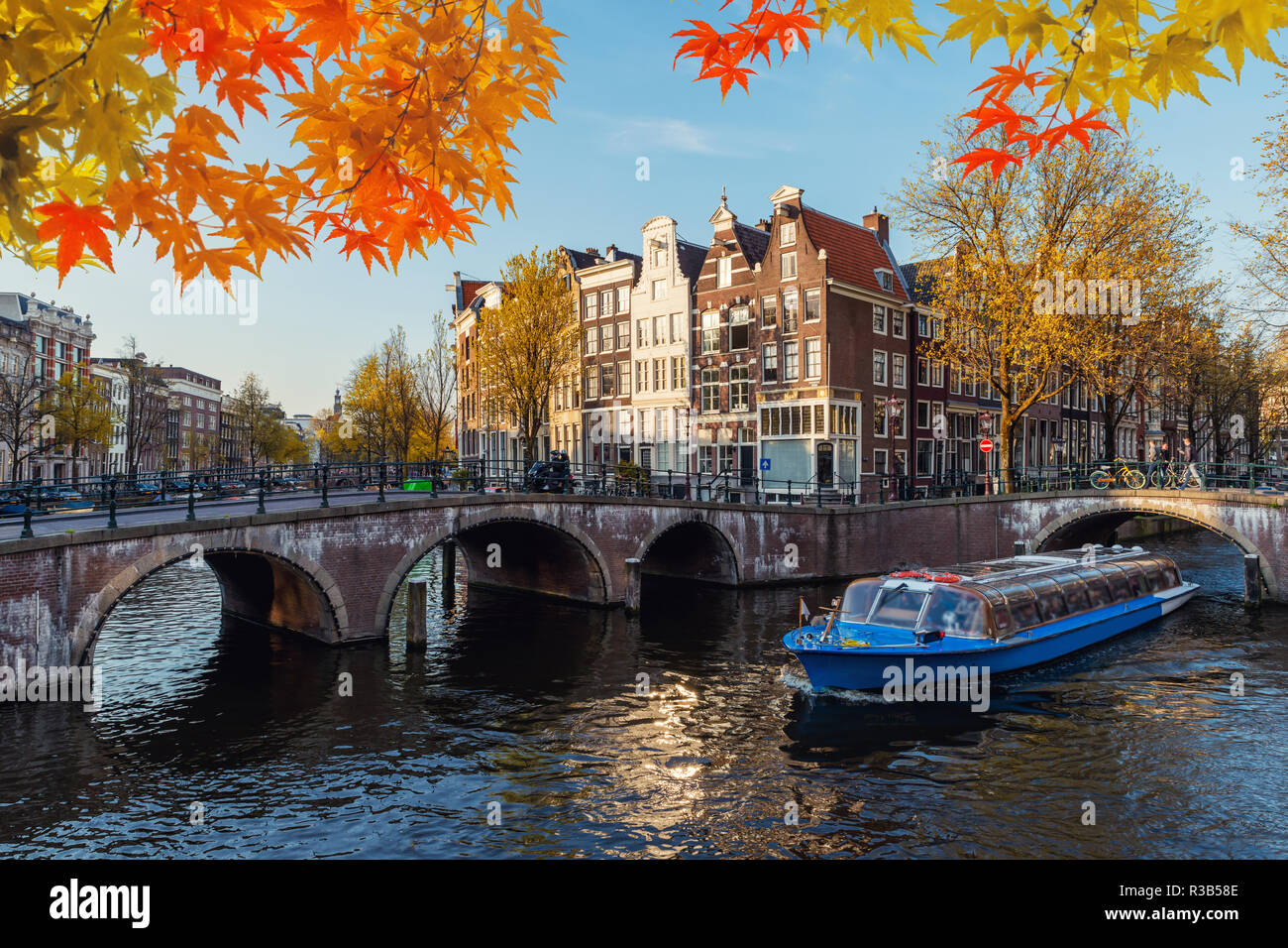 Traditional old houses on canal at fall day in Amsterdam, Netherlands at autumn season. - Stock Image