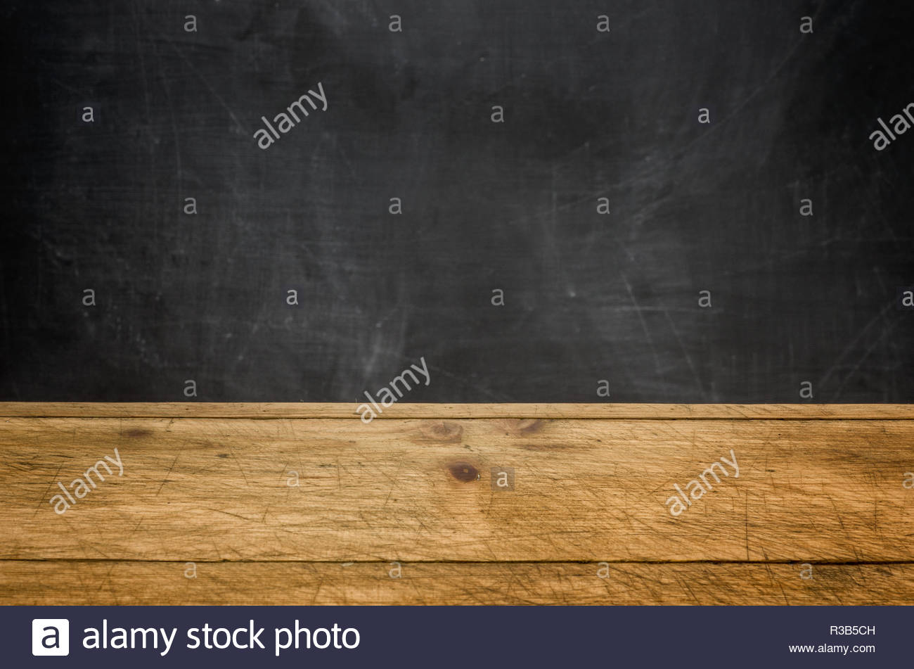 rustic wooden boards against a black wall panel - Stock Image