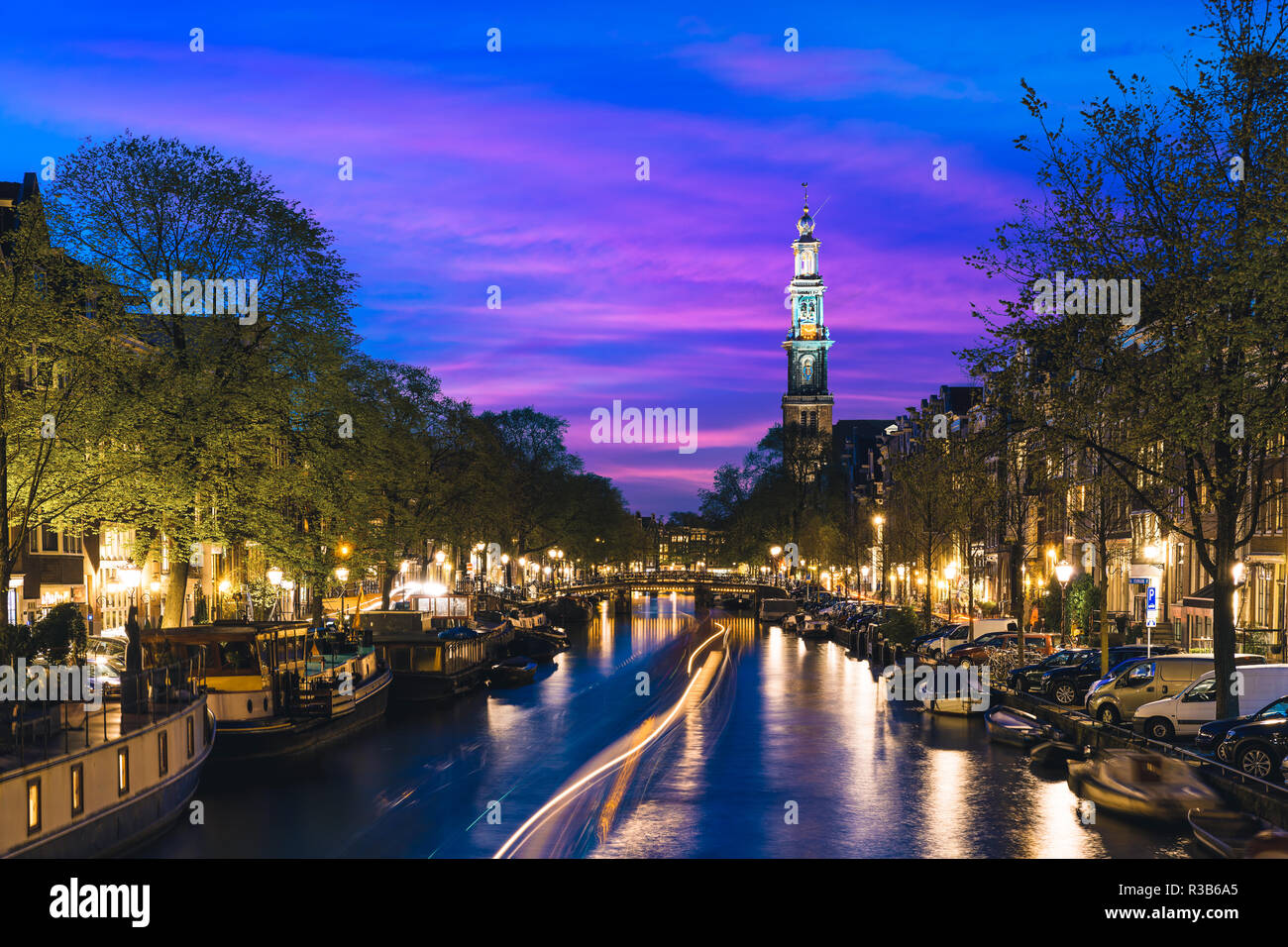 Canals of Amsterdam at night in Netherlands. Amsterdam is the capital and most populous city of the Netherlands. - Stock Image