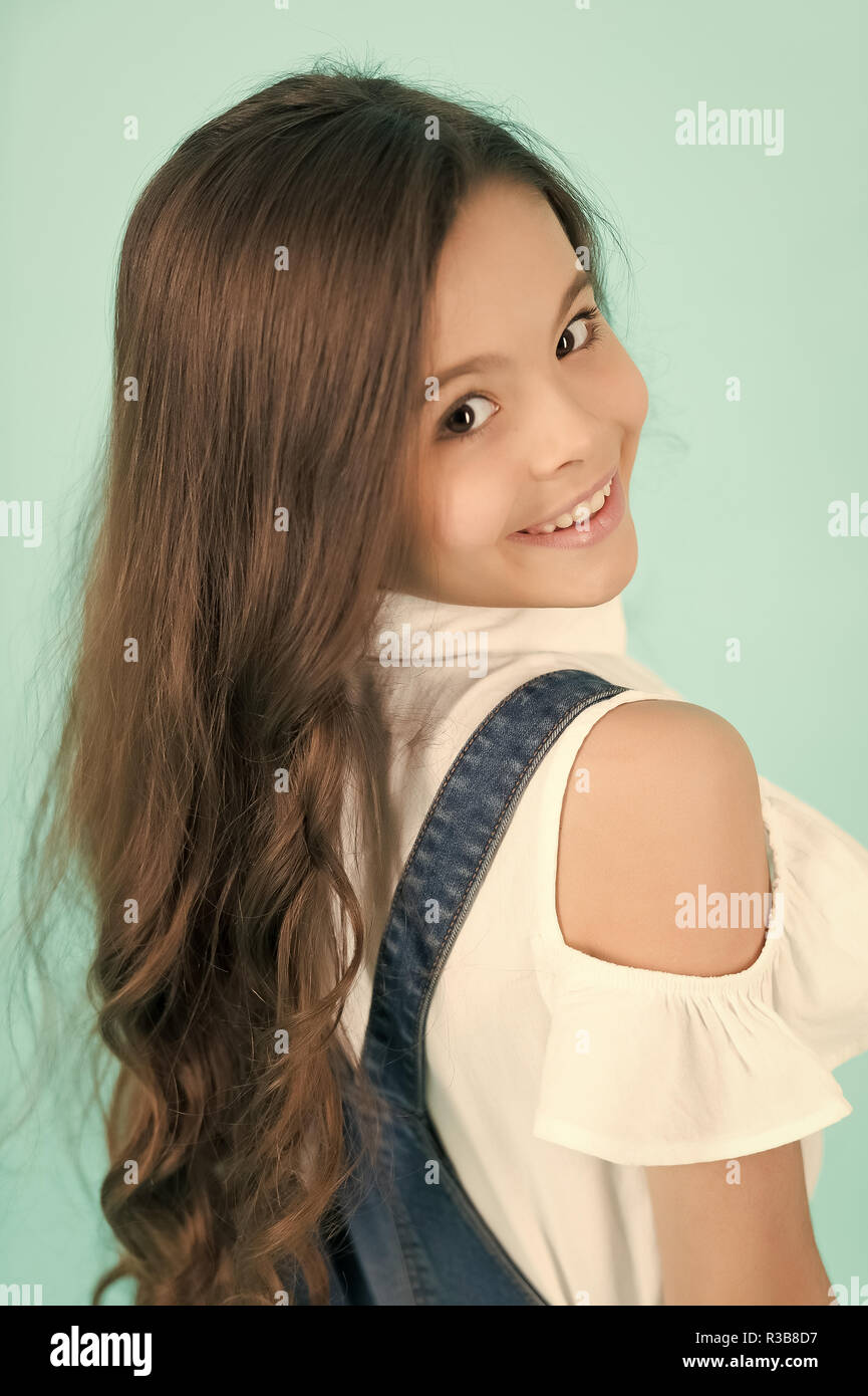 Kid Model With Long Healthy Brunette Hair Girl With Smile On Cute Face On Blue Background Beauty Look Hairstyle Youth Skincare Health Happy Child Childhood Concept Stock Photo Alamy