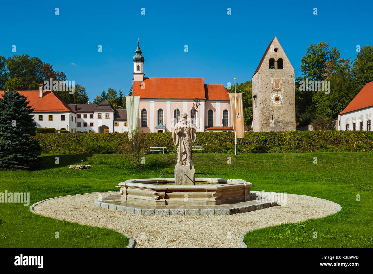 Monastery church with Roman tower and fountain with fountain figure of abbot Walto or Balto, Wessobrunn Monastery, Upper Bavaria - Stock Image