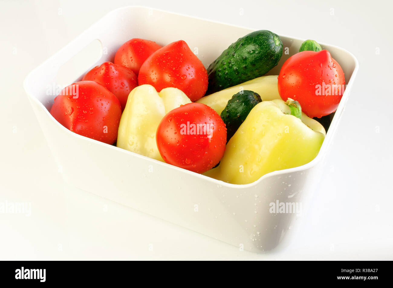 White bowl with assorted fresh vegetables on white background Stock Photo