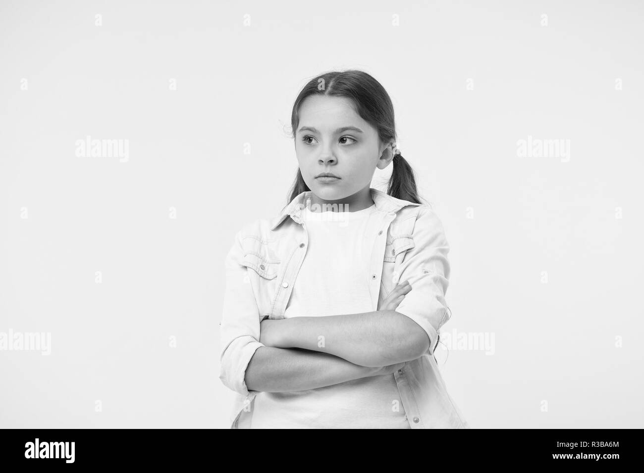 I do not want to see you. After dispute. Girl serious face offended yellow background. Kid unhappy looks strictly. Girl folded arms on chest looks serious. Sensitive girl not want to talk. - Stock Image