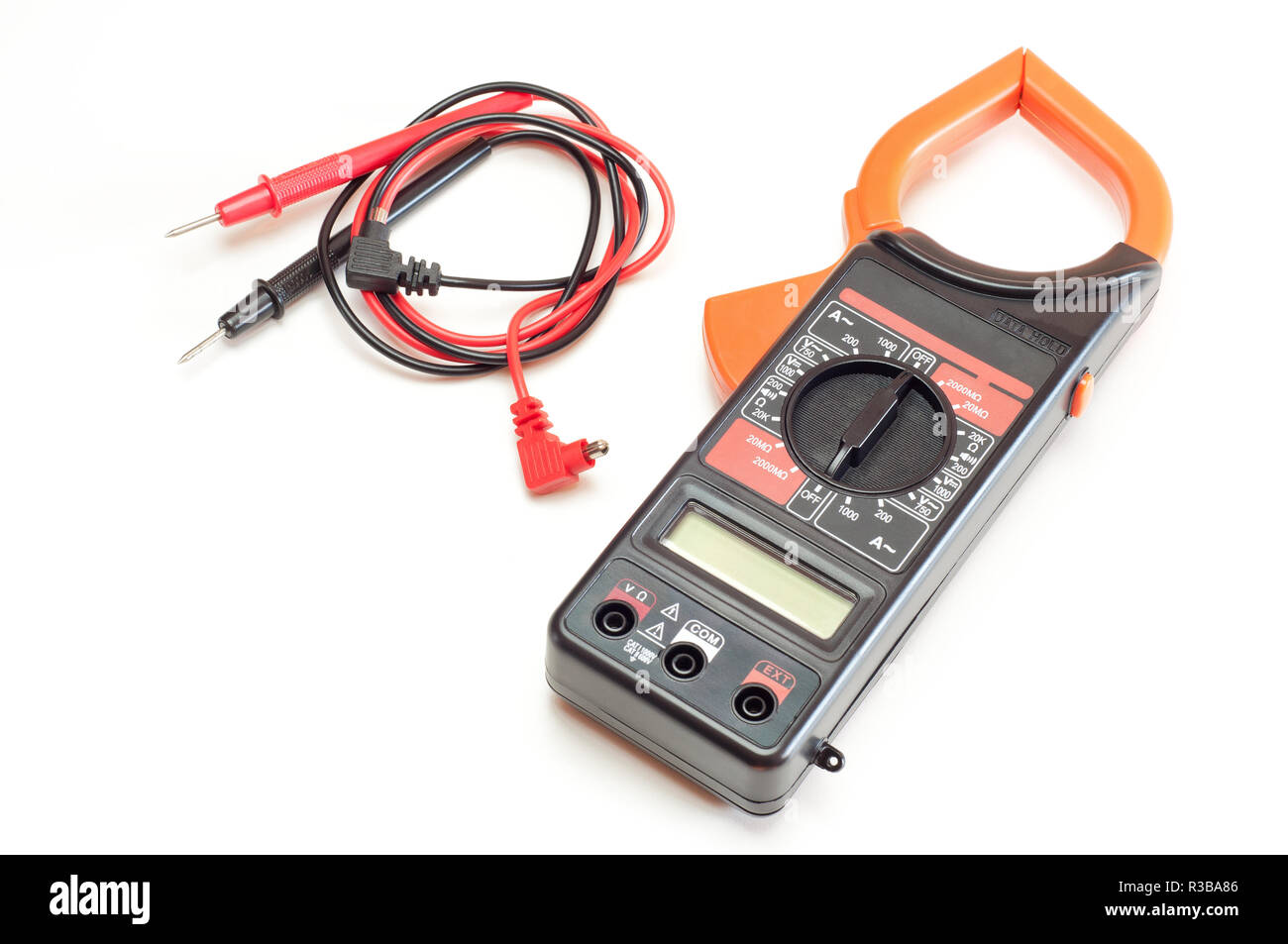 Black digital clamp meter with red and black cables, isolated - Stock Image
