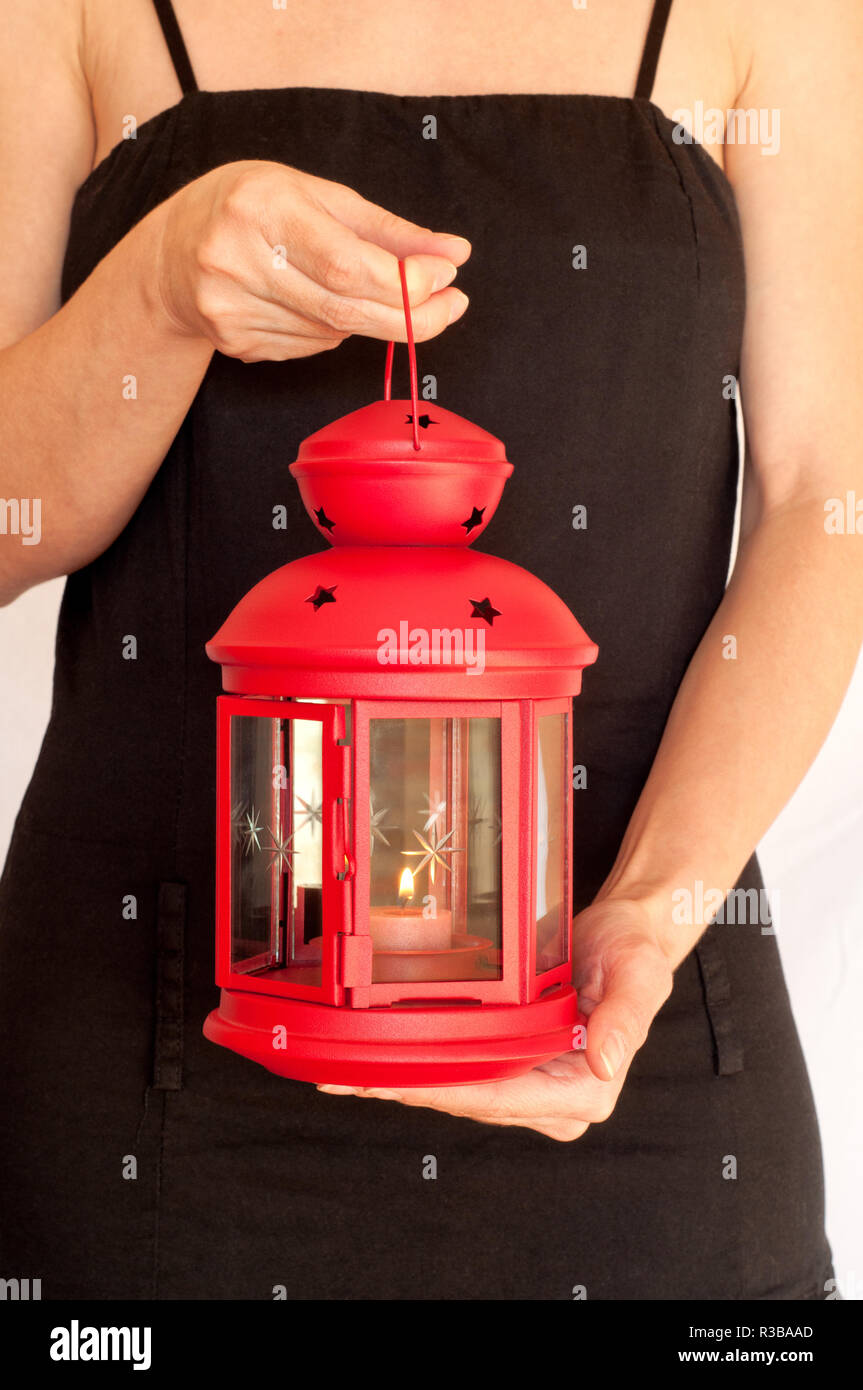 Woman holding a red lamp, studio shot - Stock Image