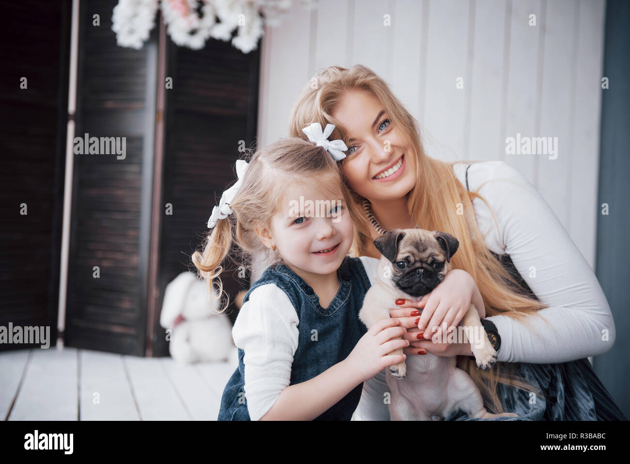 Happy loving family. Mother and her daughter child girl playing and hugging adorable pug - Stock Image