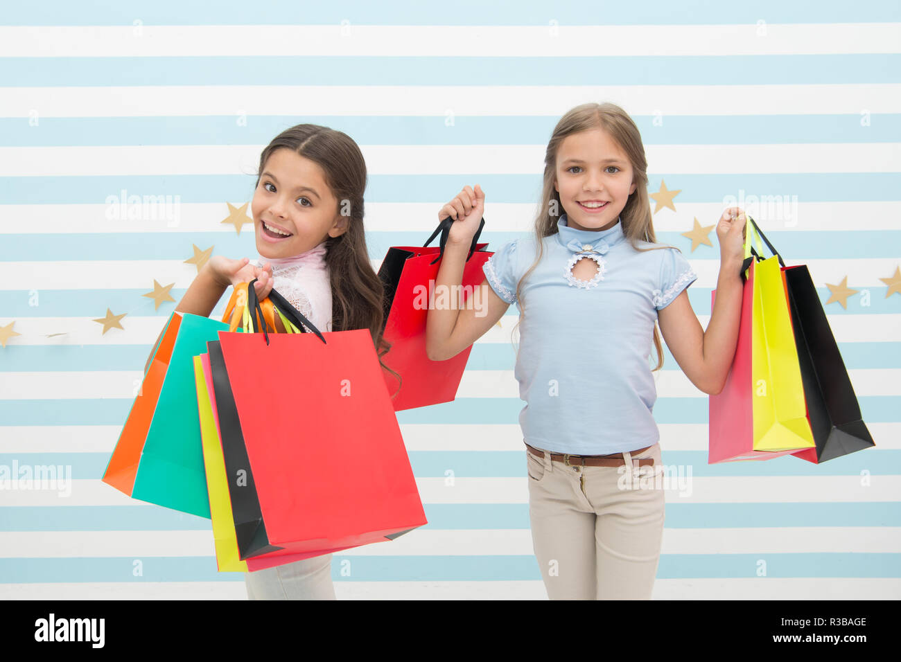 Children satisfied shopping striped background. Obsessed with shopping and clothing malls. Discount concept. Kids cute girls hold shopping bags. Shopping discount season. Spending great time together. - Stock Image