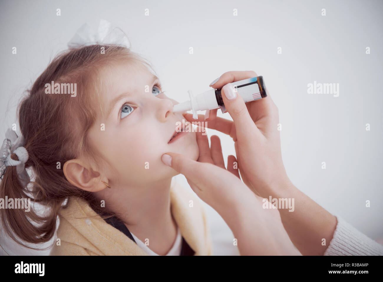the girl drips into her nose with a spray of cold - Stock Image