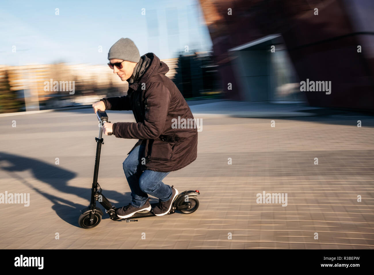 Young man in casual wear on electric kick scooter on city street in motion blur in autumn - Stock Image