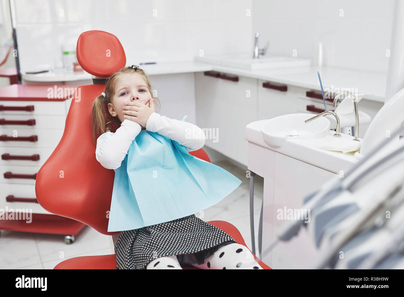 Frightened little girl at dentist office covered mouth with hands - Stock Image