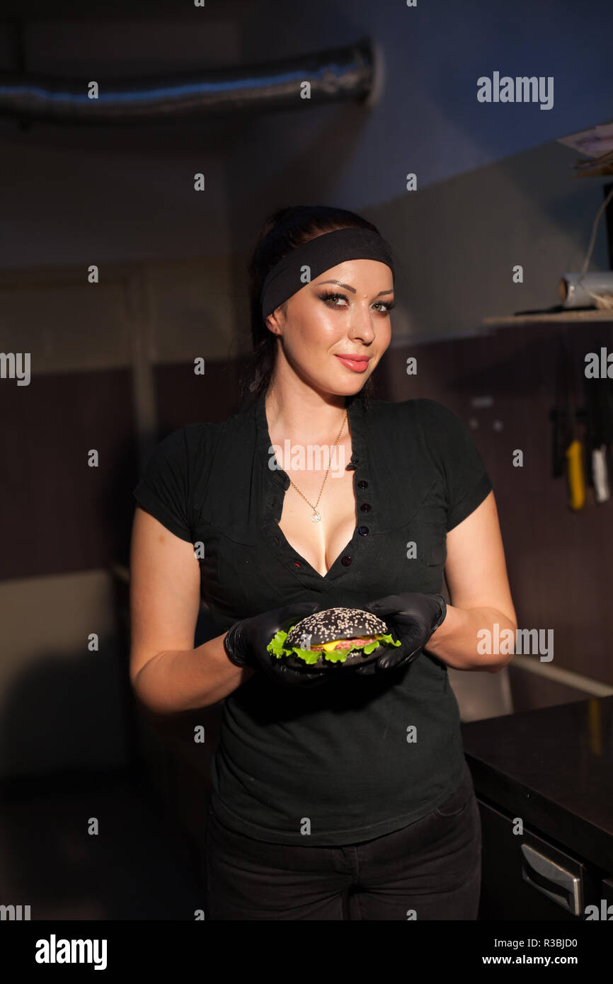 female chef preparing food in the kitchen of the restaurant Burger - Stock Image