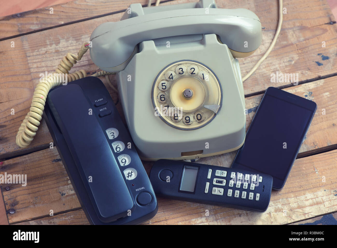 Different types of telephones landline phone, smartphone, phone with rotary on wooden board - Stock Image
