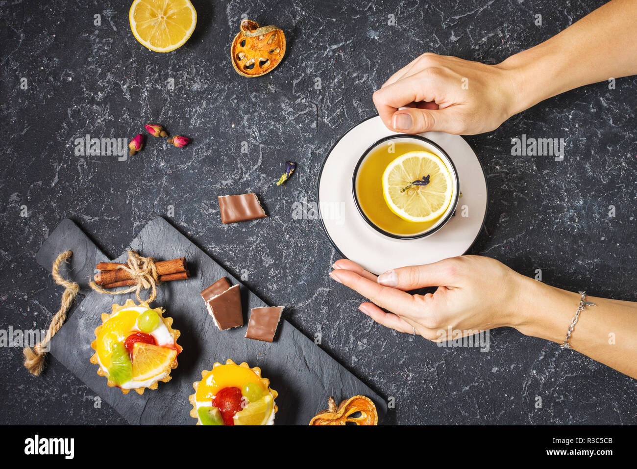 Female hands hold cup of tea on black stone background. Good morning concept. Top view - Stock Image