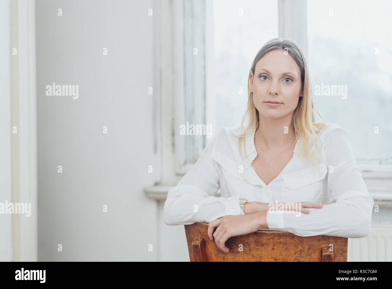Young woman sitting on a reversed chair staring at the camera with a deadpan intense expression indoors at home with copy space - Stock Image