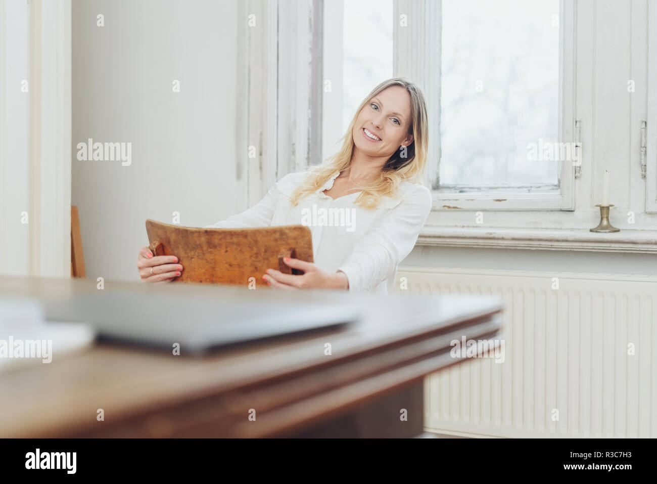 Happy relaxed woman swinging on a chair at home as she grins at the camera with a table and laptop blurred in the foreground - Stock Image