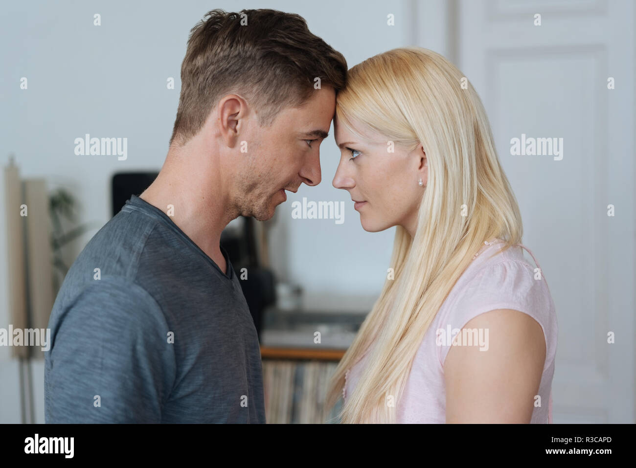 Young couple having a disagreement standing head to head glaring at each other indoors at home - Stock Image