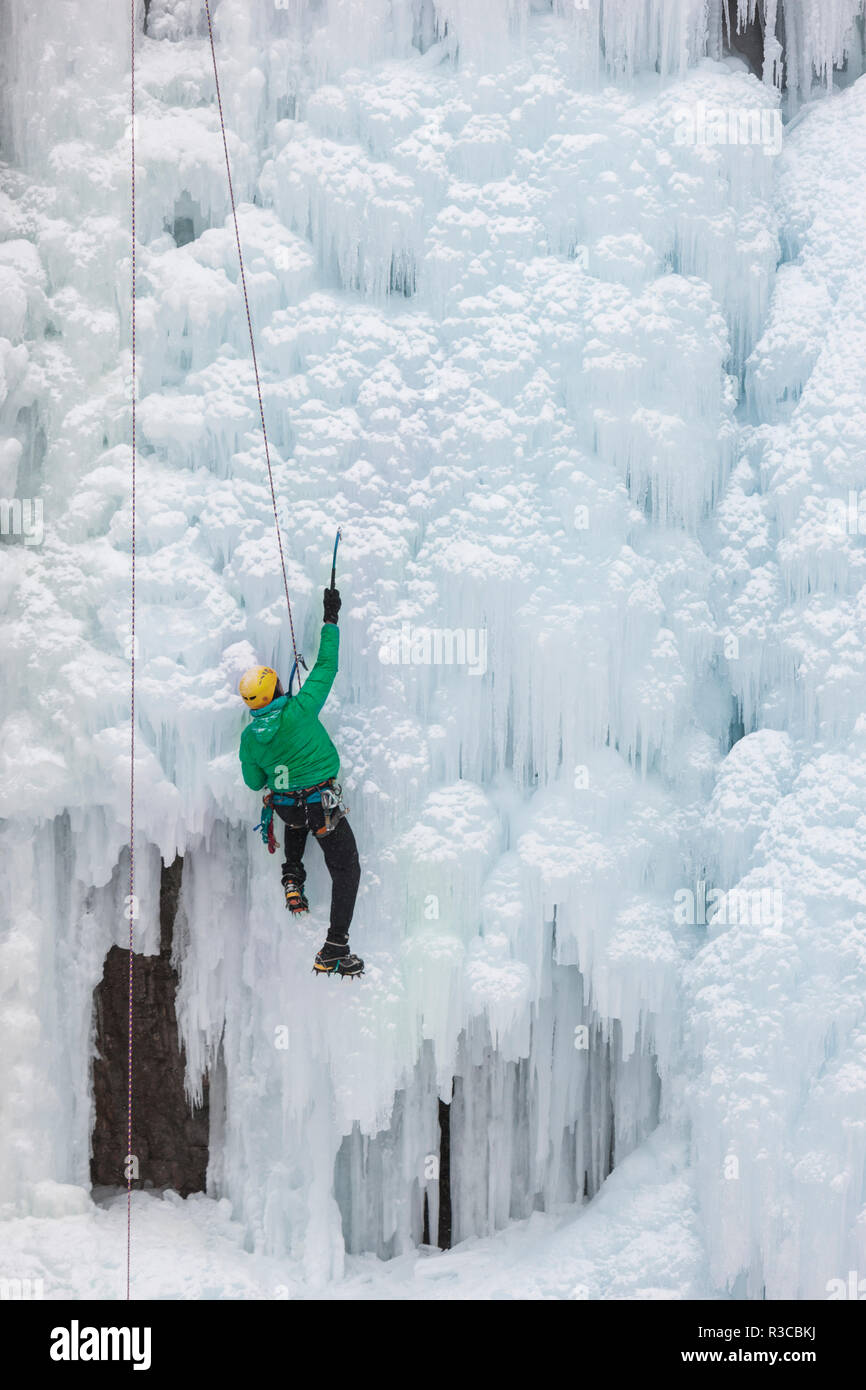 USA, Colorado, Uncompahgre National Forest. Climber ascends icy cliff face. - Stock Image
