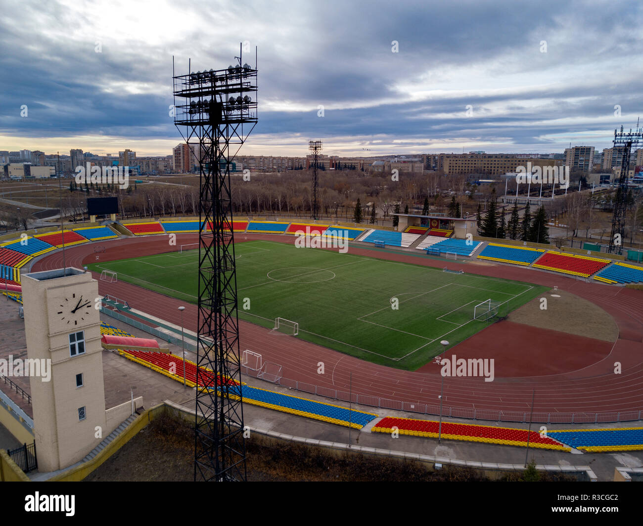 Aerial view of central football stadium and summer athletics classes place in the provincial city; bright tribunes for local competitions; inclement w - Stock Image