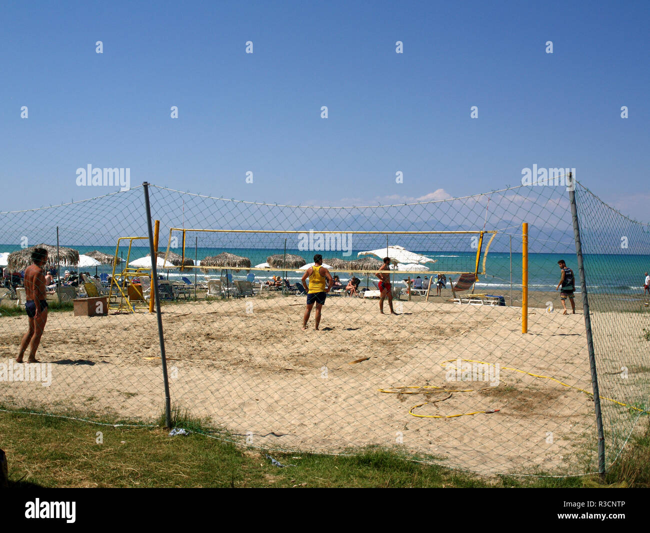Tourists playing on volley ball court next to the beach road in Roda, Corfu, Greece - Stock Image