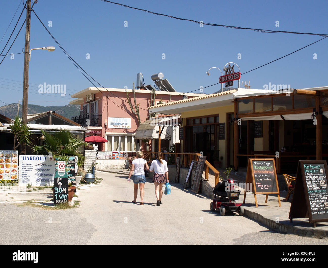 Tourists walking along the beach road in Roda, Corfu, Greece between Crusoes Pub and The Harbour Bar - Stock Image